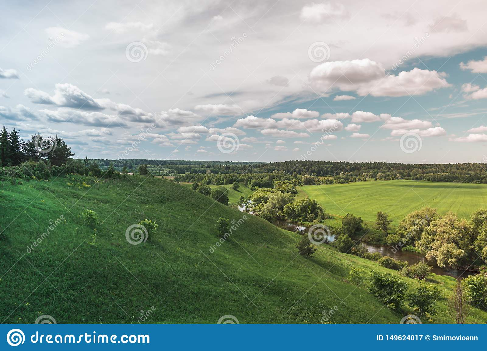 Colorful Bright Sunny Green Field River Summer Landscape With Blue Cloudy Sky, Trees And Hills