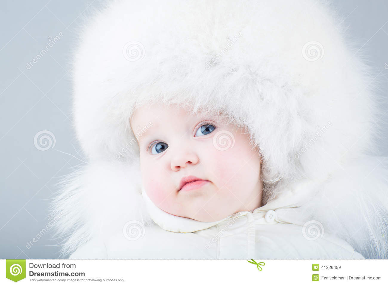 Very Funny Baby In A White Snow Suit And Big Fur Hat Stock