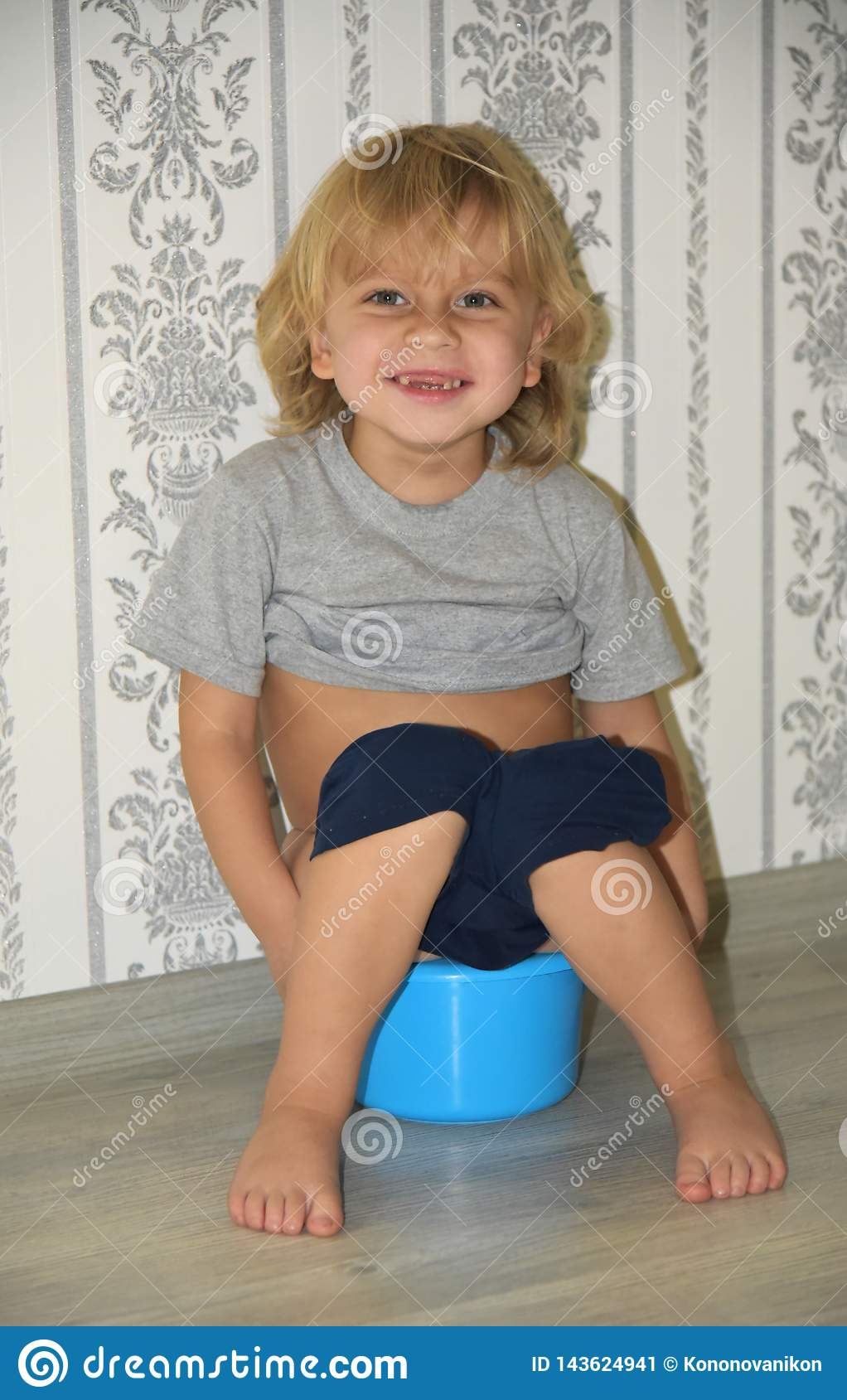Very happy little boy 4 years old sitting on the potty and smiles. Portrait of a blond boy