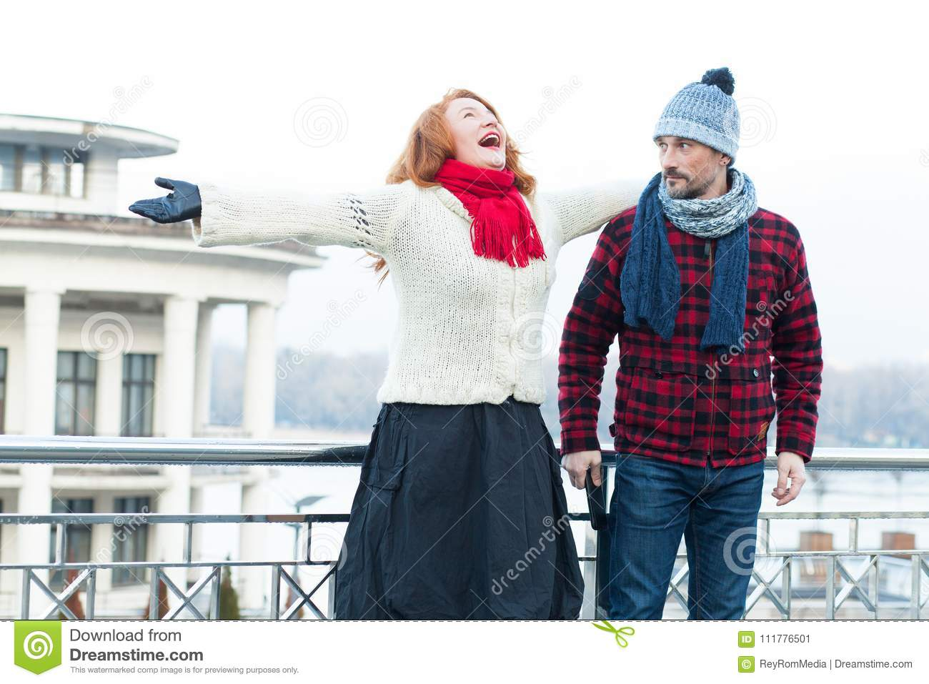 Screaming red hair woman and guy looking to her. Very happy woman crying on the bridge and surprised man.