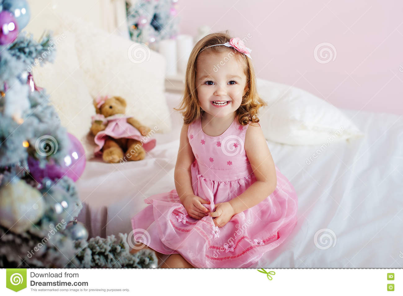 little naked girl Very nice charming little girl blonde in pink dress sitting on a child`s bed