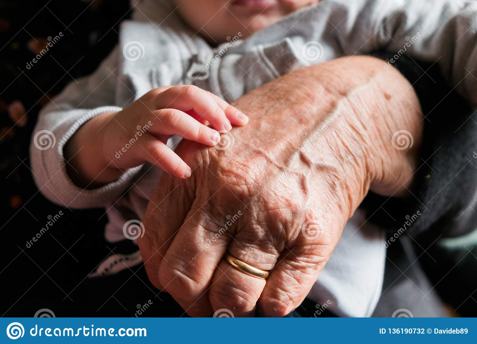 Small baby hand touching and caressing old grandmother hand with wrinkles, symbol of passing generations