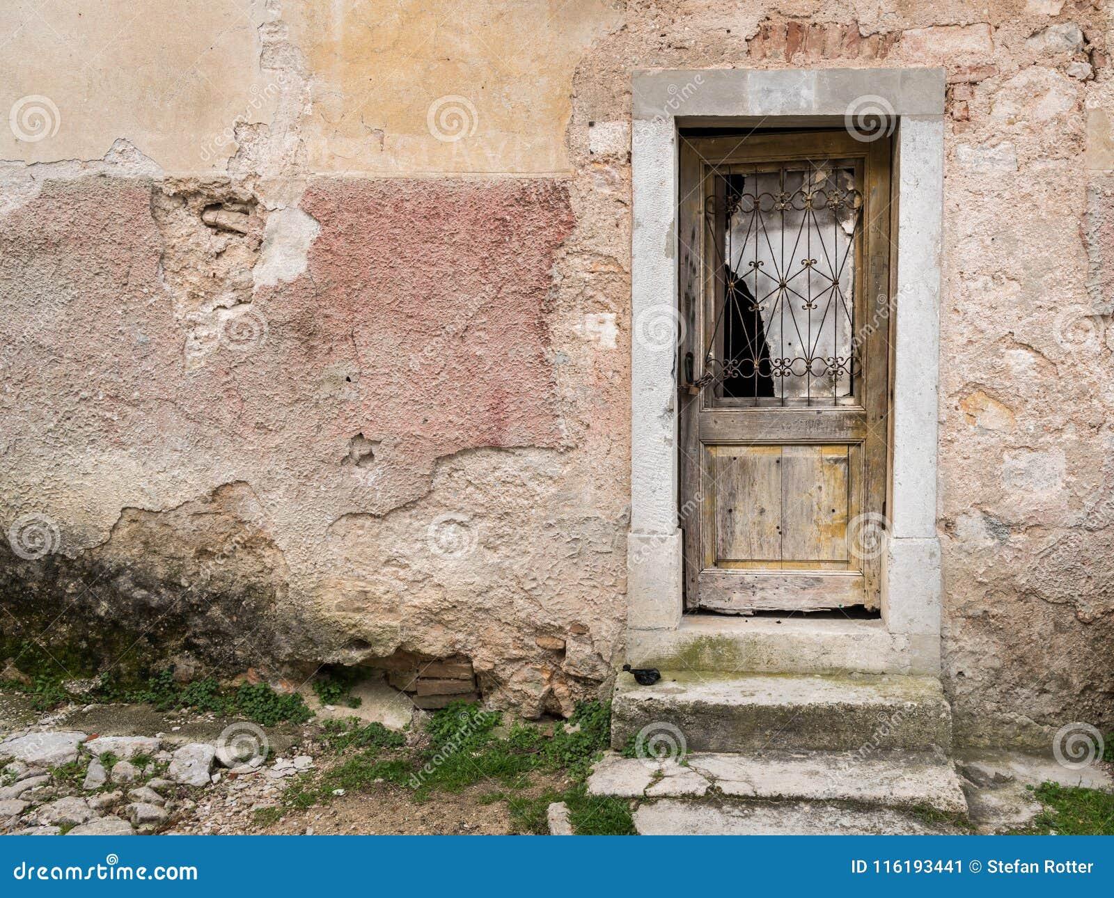 Very old weathered door made of wood, broken glass