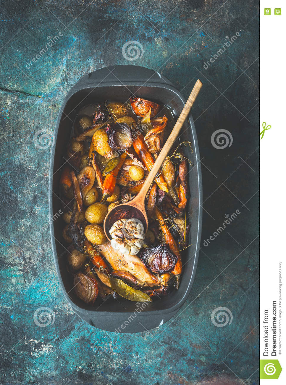 Very rustic roasted vegetables stew or ragout with wild game and wild fowl and forest mushrooms in black backing dish with wooden