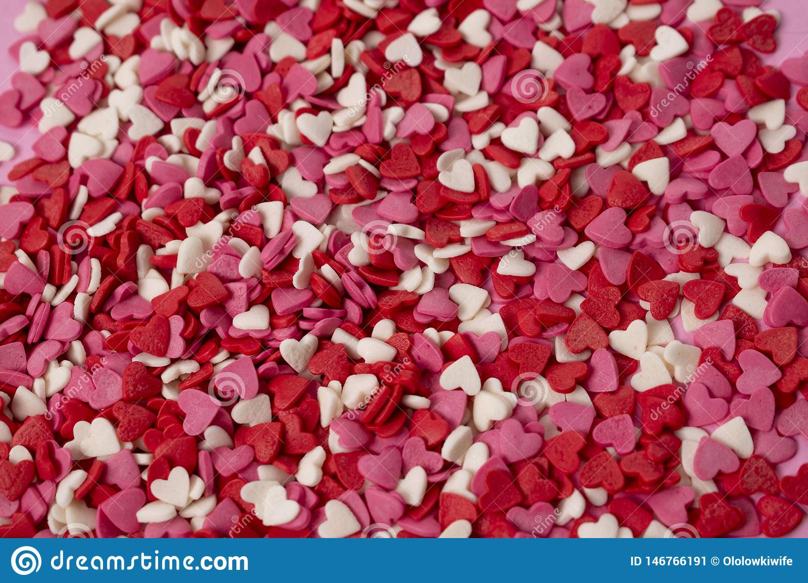 Very small heart-shaped candies are scattered across the background. Many small bright hearts in bulk