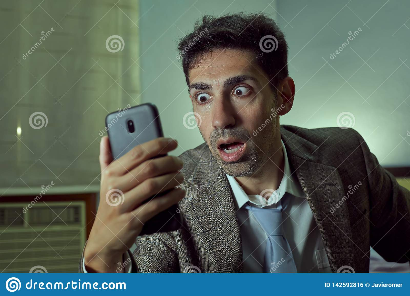 Very surprised man looking at his smartphone in a room