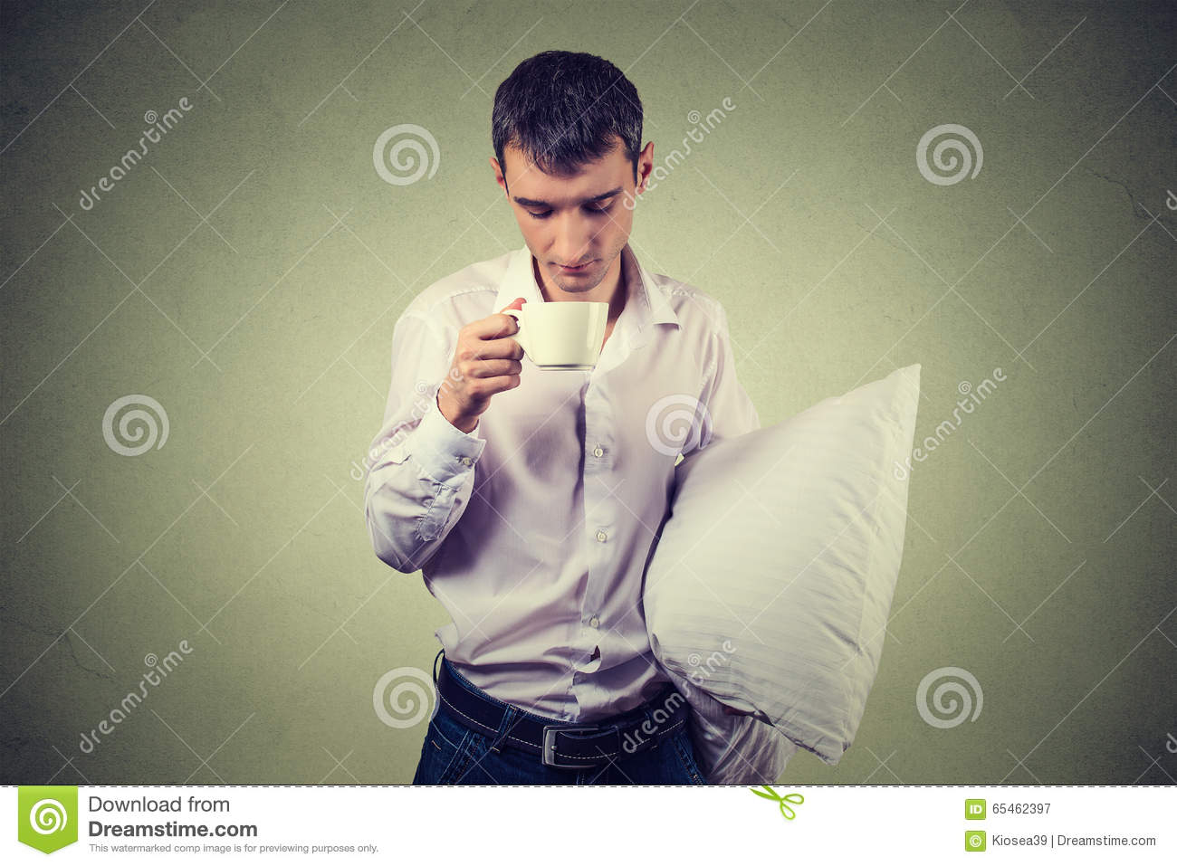 Very tired, falling asleep business man holding a cup of coffee and pillow