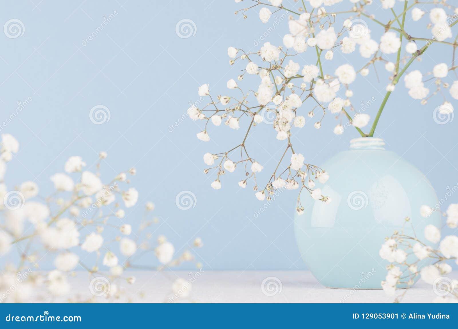 Verzacht elegant boeket van kleine bloemen in ceramische cirkelkom op zachte pastelkleur blauwe achtergrond