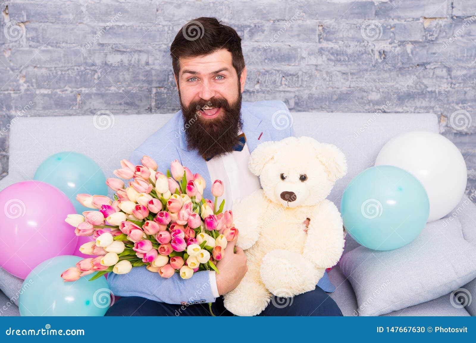 Verzend bloemen als u betekenen het Bloem voor 8 Maart De gebaarde mens met tulpenboeket en draagt De datum van de liefde interna