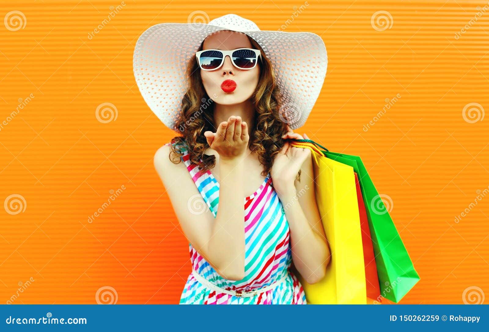 Verzendt de portret mooie vrouw die rode lippen blazen zoete luchtkus met het winkelen zakken die kleurrijke gestreepte kleding,