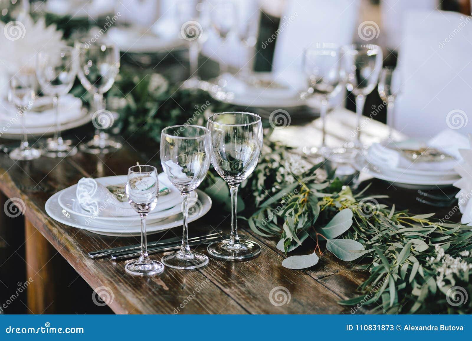 Verzierte elegante hölzerne Hochzeitstafel in der rustikalen Art mit Eukalyptus und Blumen, Porzellanplatten, Gläser, Servietten