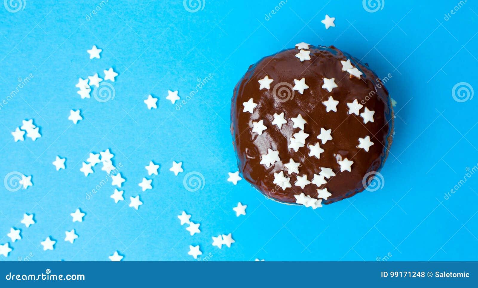 Verzierter Schokoladendonut auf blauem Hintergrund