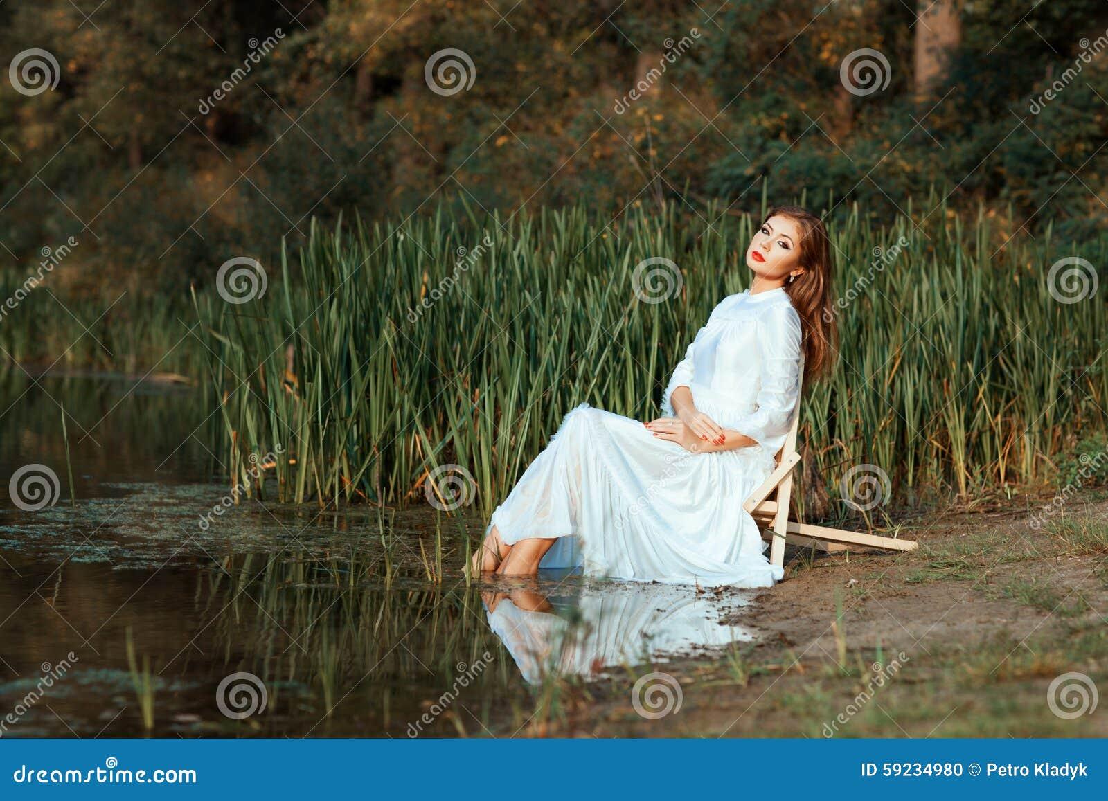 Vestido blanco de la muchacha que se sienta sumergiendo pies en el lago