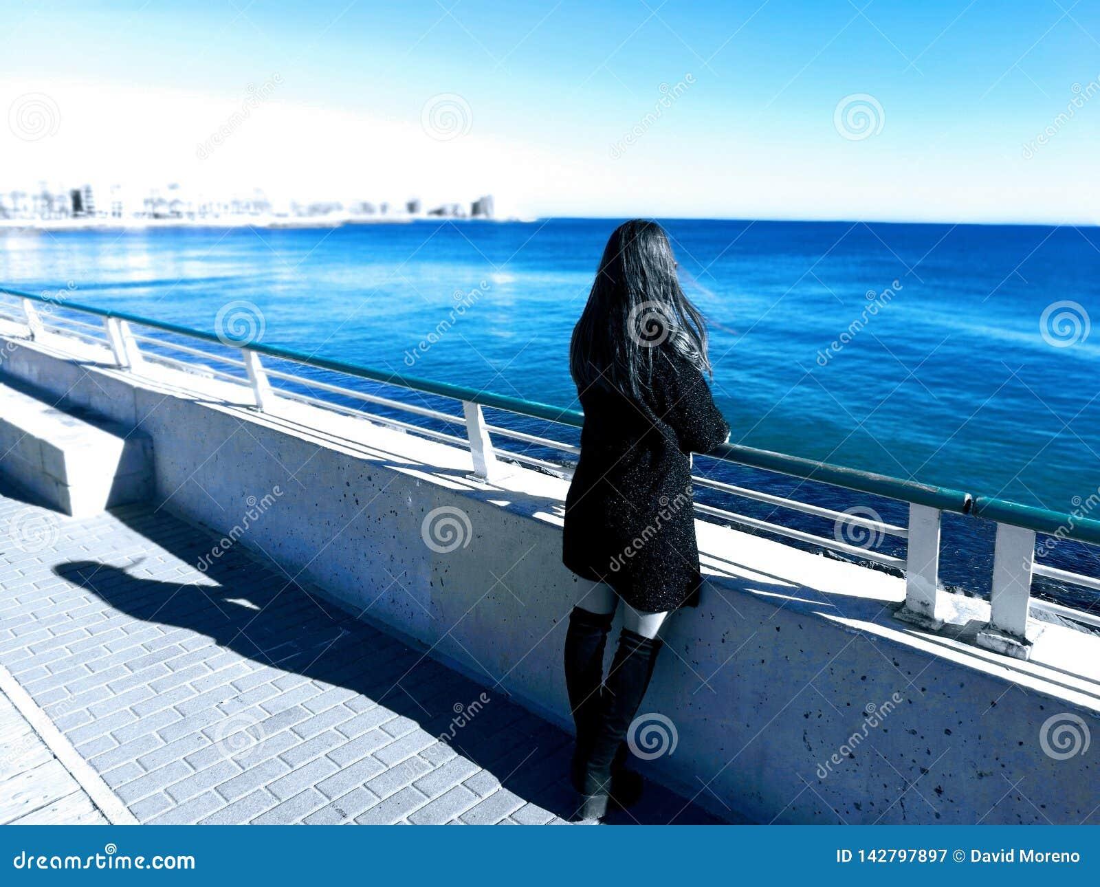 Vestido bonito do preto do girlin que olha fixamente na praia Conceito do mundo de fantasia
