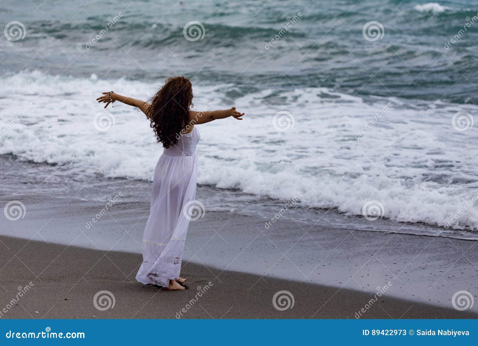 Vestido branco vestindo da mulher e apreciação da tempestade do mar