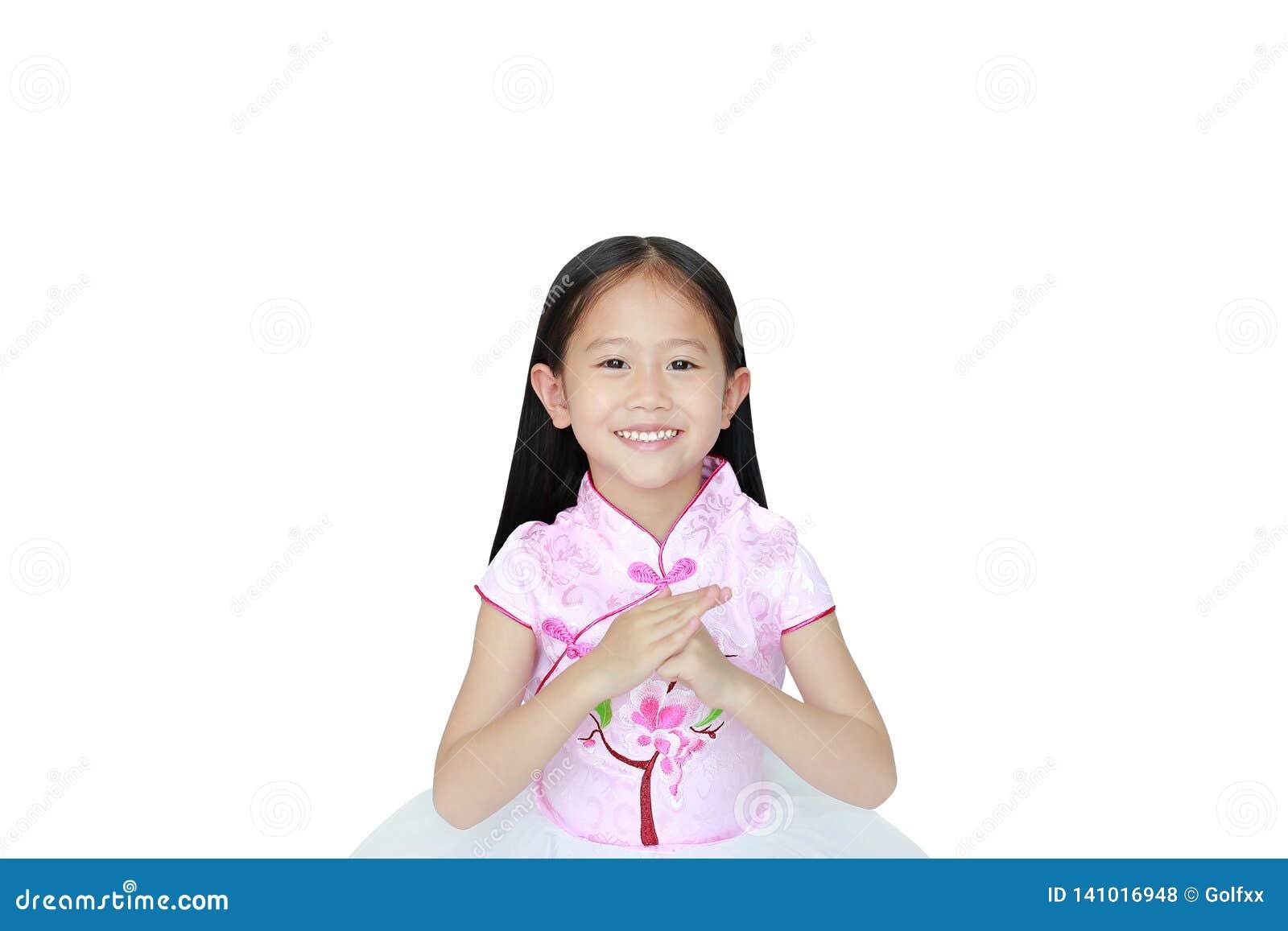 Vestido chinês tradicional vestindo do rosa da menina asiática pequena feliz da criança com celebração do gesto do cumprimento pe