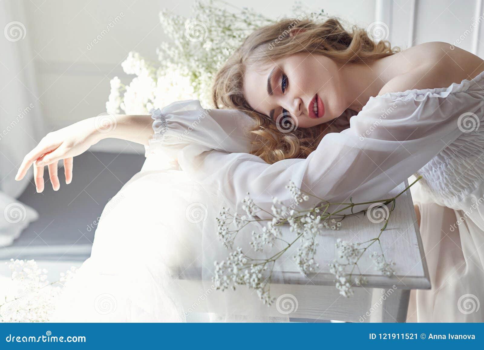 Vestido de la luz blanca de la muchacha y pelo rizado, retrato de la mujer con las flores en casa cerca de la ventana, pureza e i