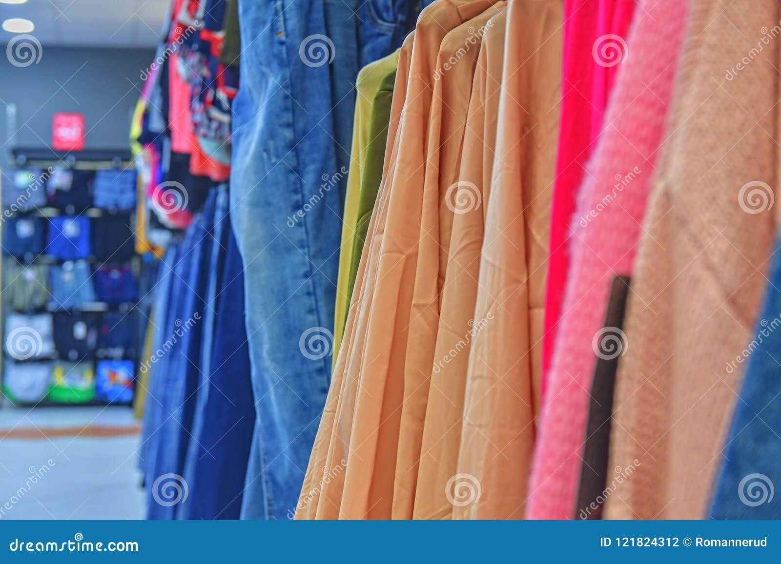 46b52d333 Vestido do traje da loja de roupa Loja da forma conceito do estilo O `  colorido s das mulheres veste-se em ganchos em uma loja varejo Conceito da  forma e da ...