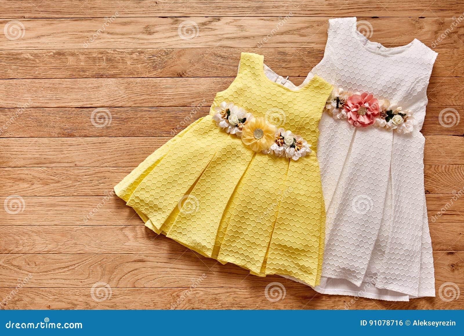 Vestido Hermoso Dos Para Las Niñas En Fondo De Madera Foto
