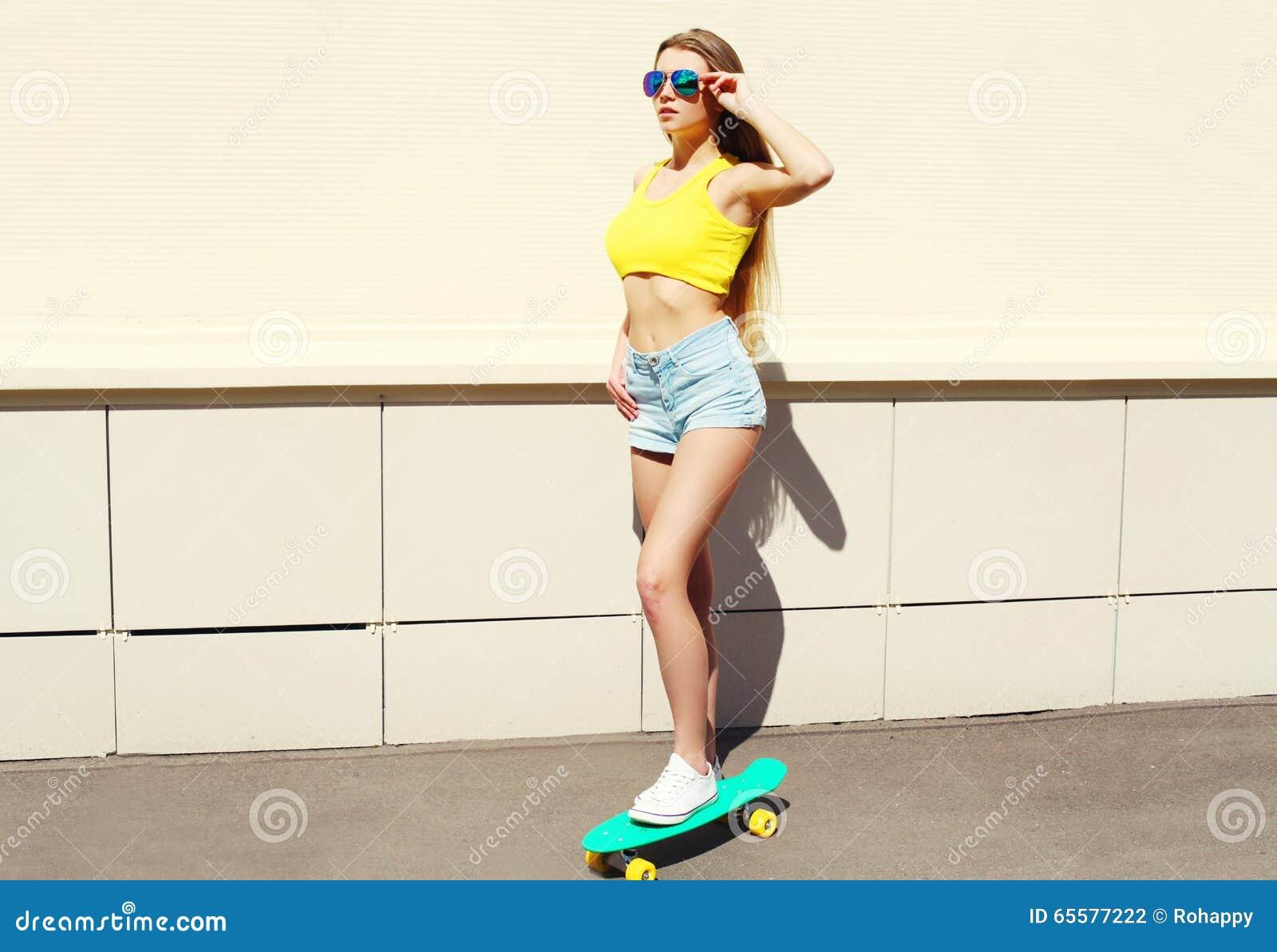 Vestir bonito bonito da menina óculos de sol e short no skate