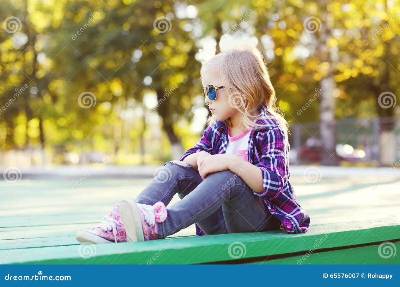 Vestir da criança óculos de sol e camisa quadriculado que sentam-se na cidade