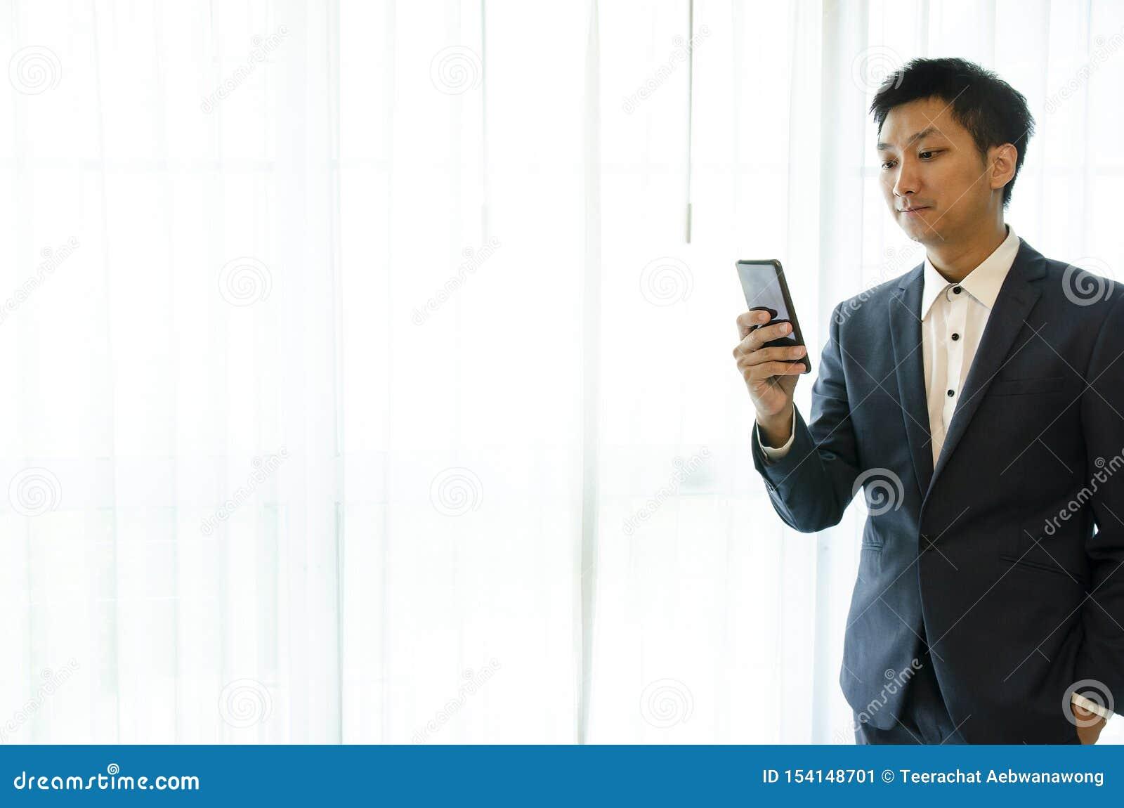 Vestito d uso dell uomo di affari, guardante smartphone Ufficio del sottotetto dello spazio aperto Fondo panoramico delle finestr