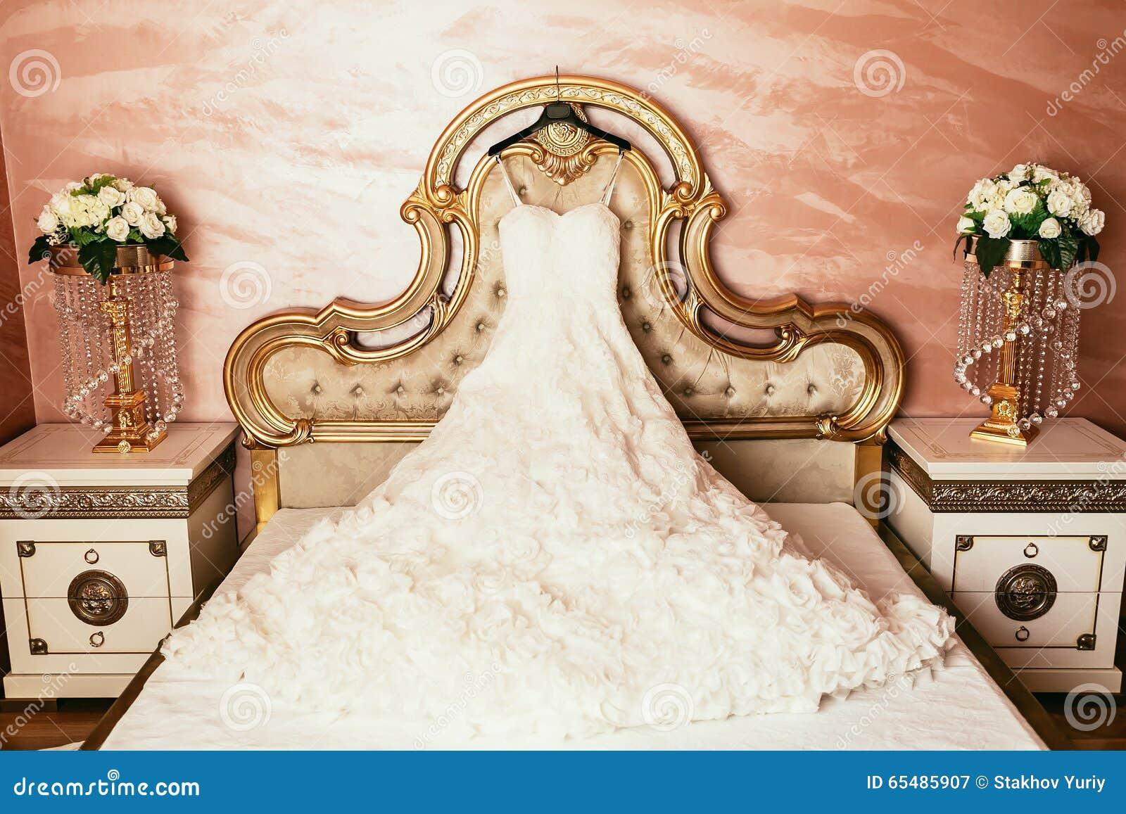 Vestito da sposa che appende sul letto di lusso decorato - Giochi da baciare sul letto ...