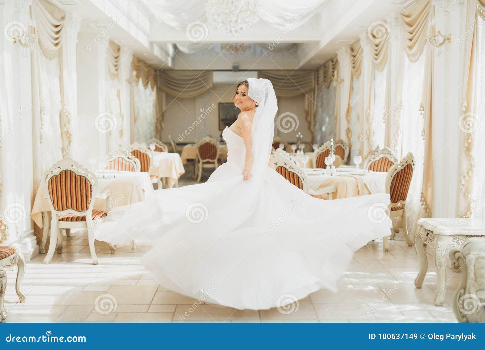Vestito da sposa d uso da modo della bella sposa con le piume con trucco di delizia e l acconciatura di lusso, studio dell intern