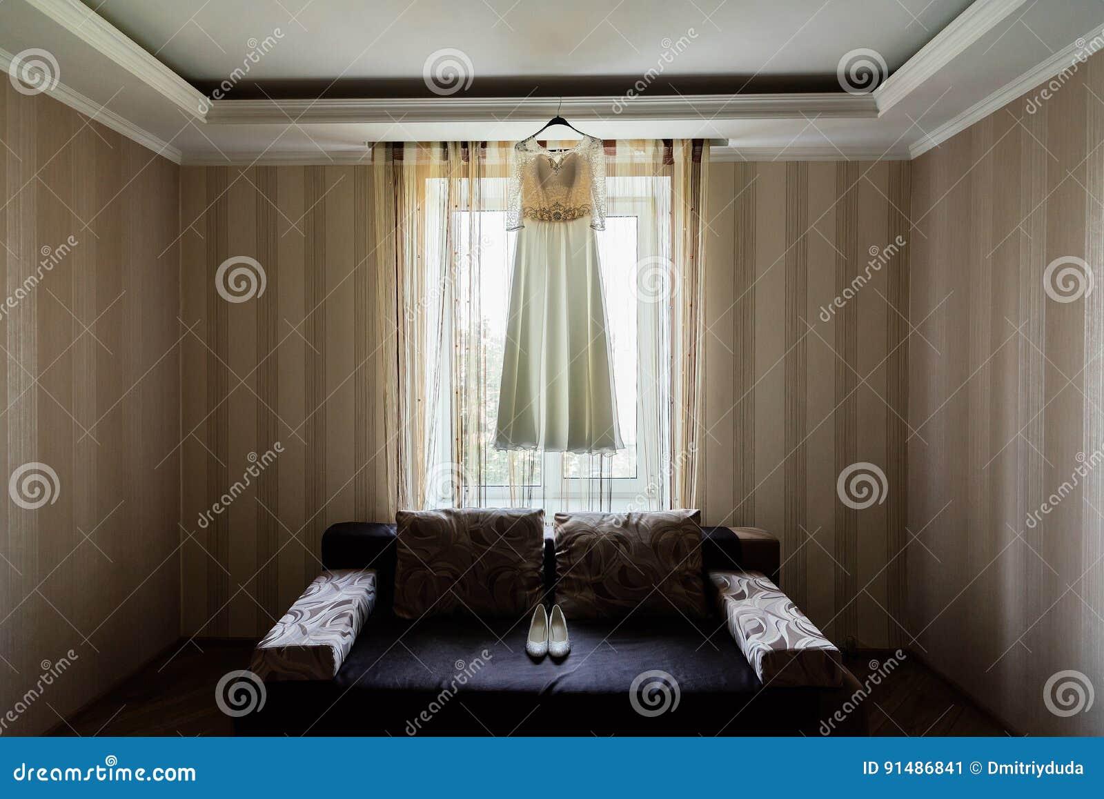 Vestito dal ` s della sposa che appende sullo scaffale vicino alla finestra nella stanza