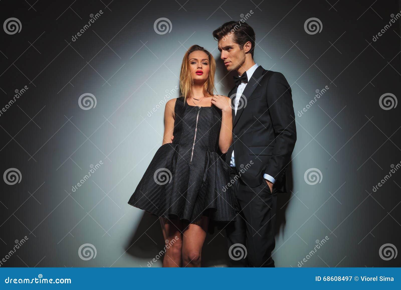 91f7920c5b8a Coppie nel nero che posa insieme nel fondo grigio dello studio le donne sta  riparando il suo vestito mentre esaminavano la macchina fotografica gli  uomini ...