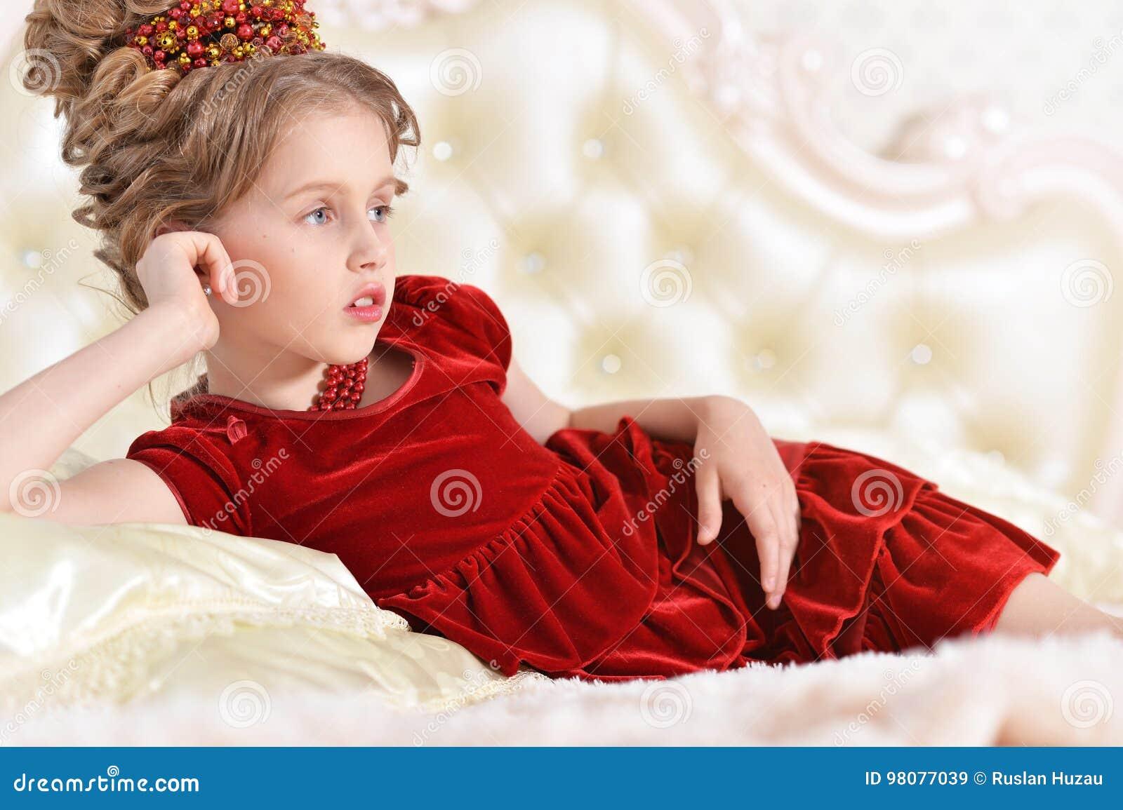 0eba9c5577 Bambina sveglia in vestito rosso dal velluto con la retro acconciatura che  si trova sullo strato beige