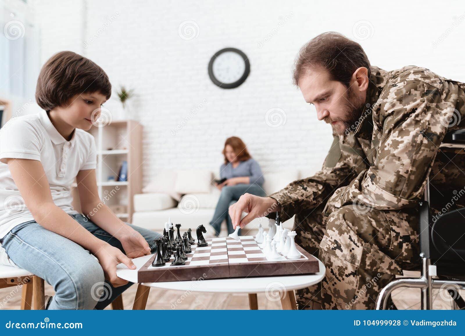 Veteran i militär likformig i en rullstol En handikappade personerman spelar med hans son i schack