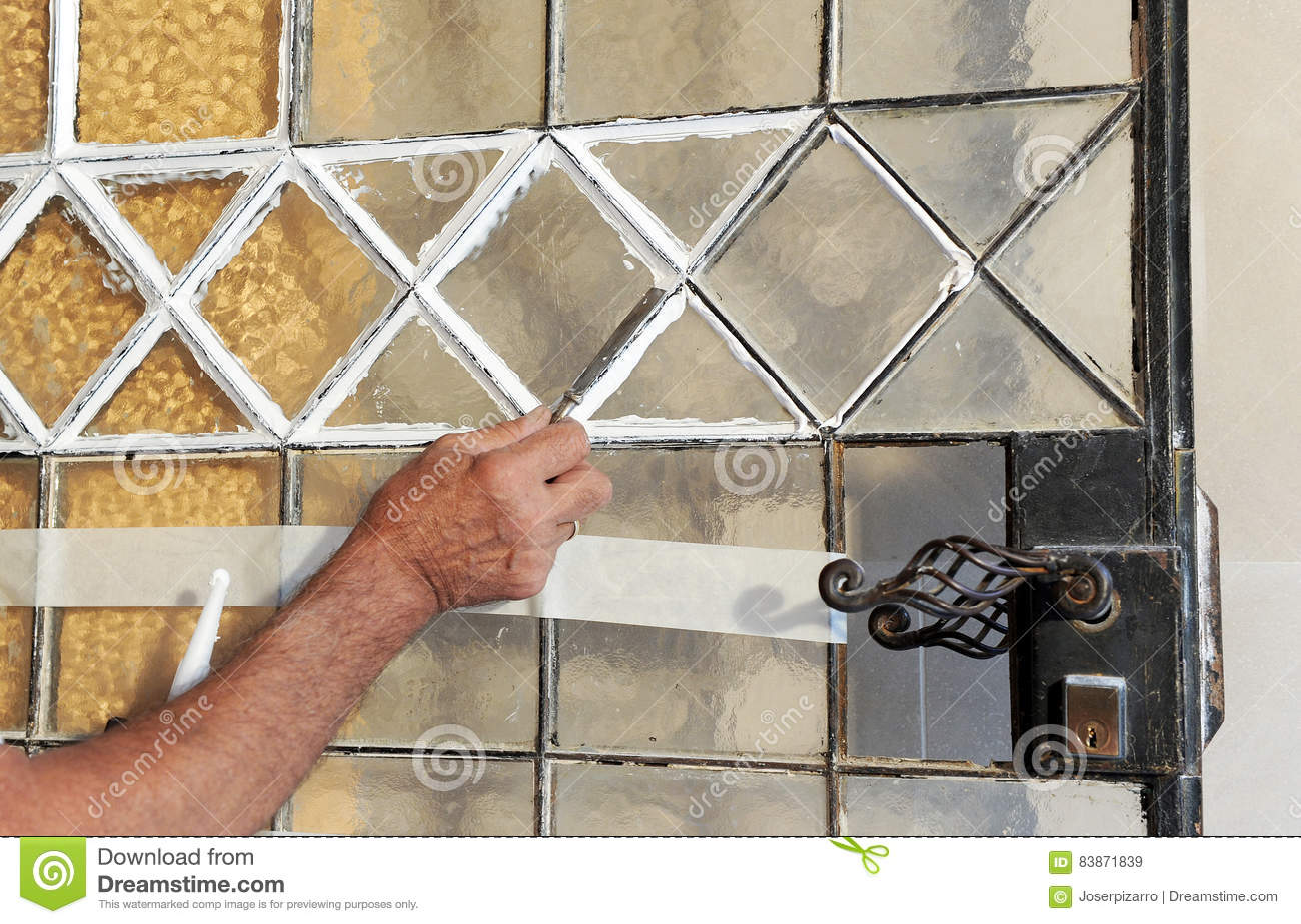 Il Mastice Del Vetraio.Vetraio Che Cambia I Cristalli Di Vecchia Porta Immagine Stock