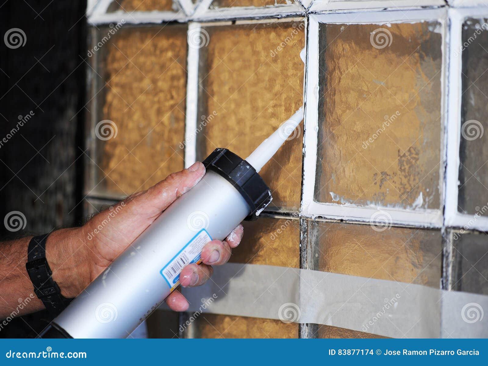 Il Mastice Del Vetraio.Vetraio Che Dispone I Cristalli Di Vecchia Porta Con Una Pistola Del