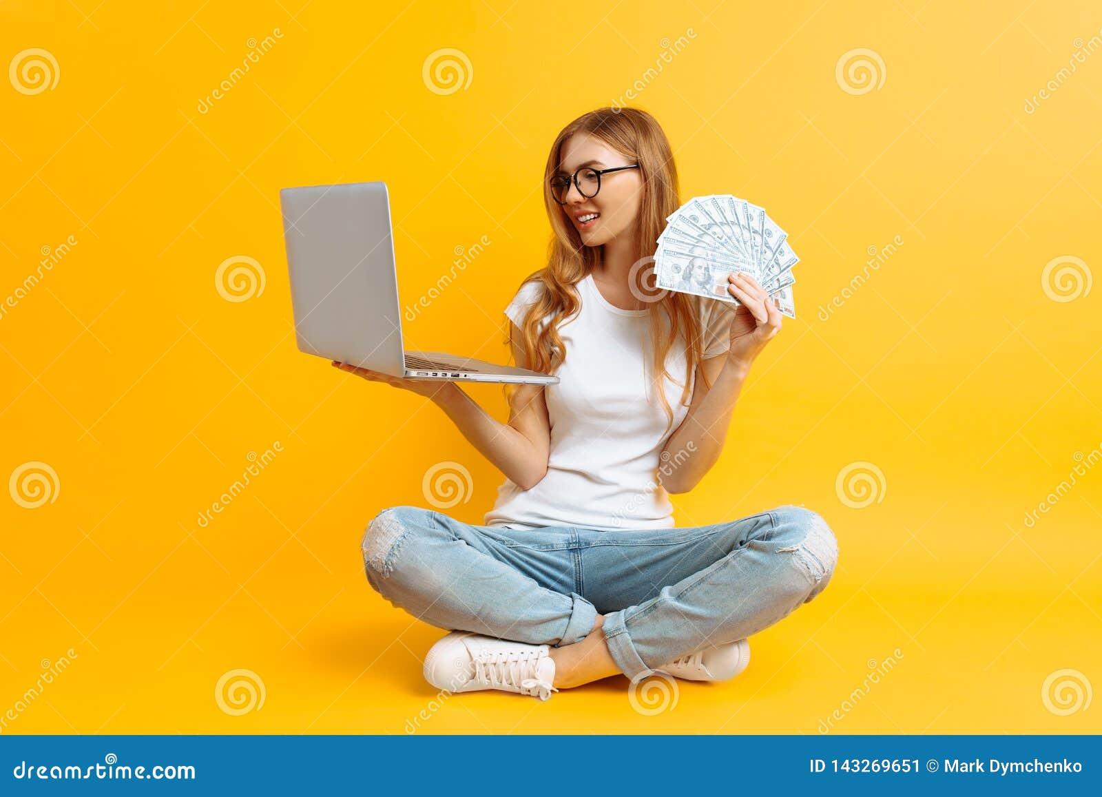 Vetri d uso della donna che si siedono sul pavimento facendo uso di un computer portatile portatile e che tengono soldi in sua ma
