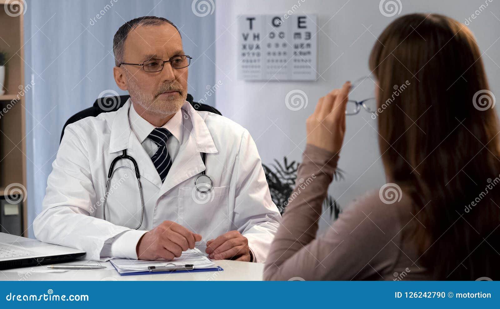 Vetri d uso della donna, oftalmologo che guarda e che contribuisce per scegliere gli occhiali