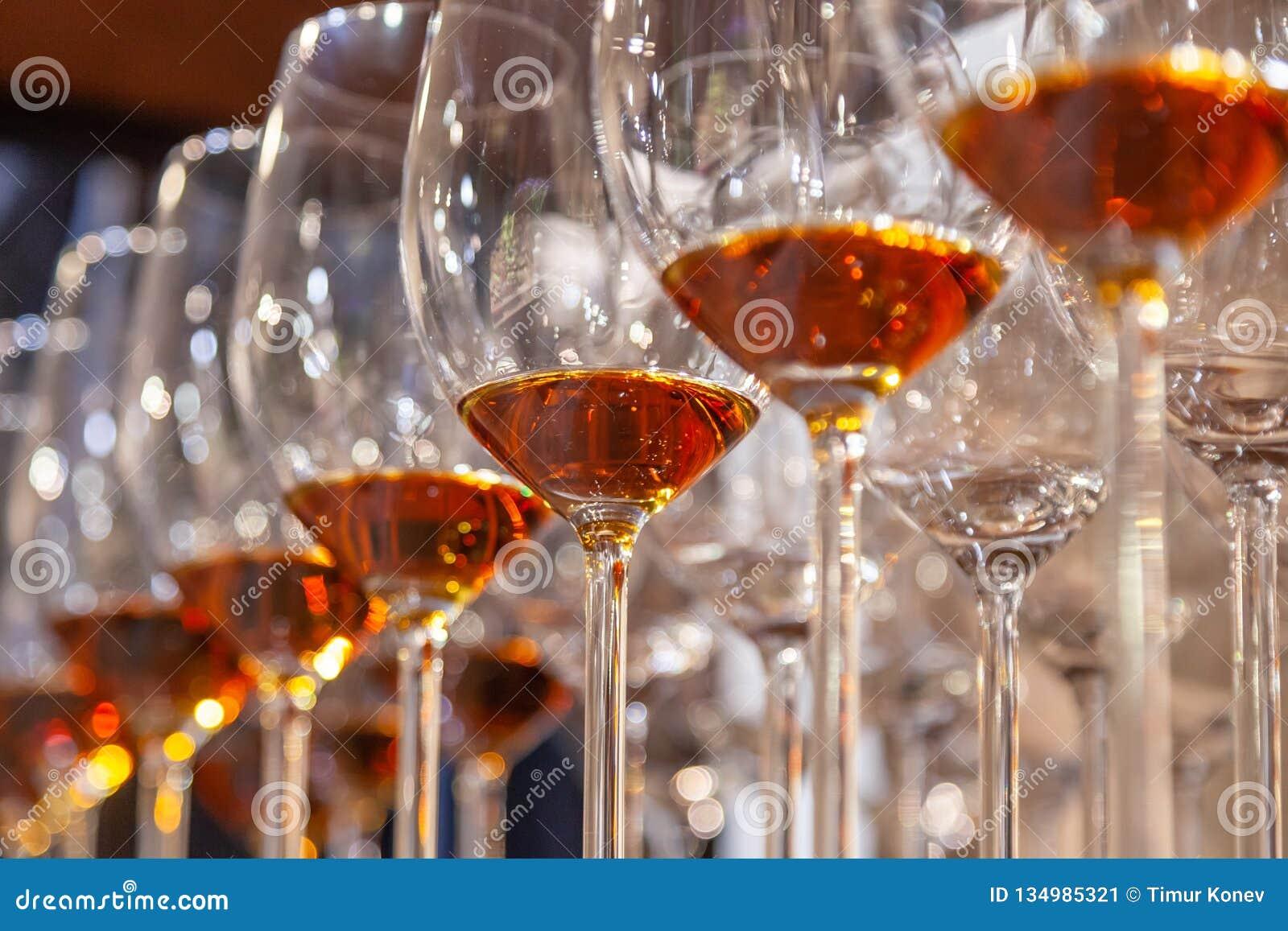 Vetri del primo piano con il supporto del cognac nella linea Sotto la vista Brandy del whiskey di alcoolici di degustation di con