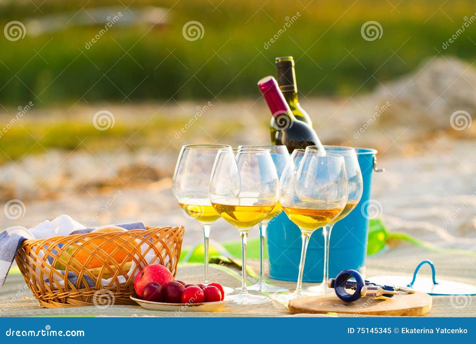 Vetri del vino bianco sulla spiaggia sul tramonto, tema di picnic,