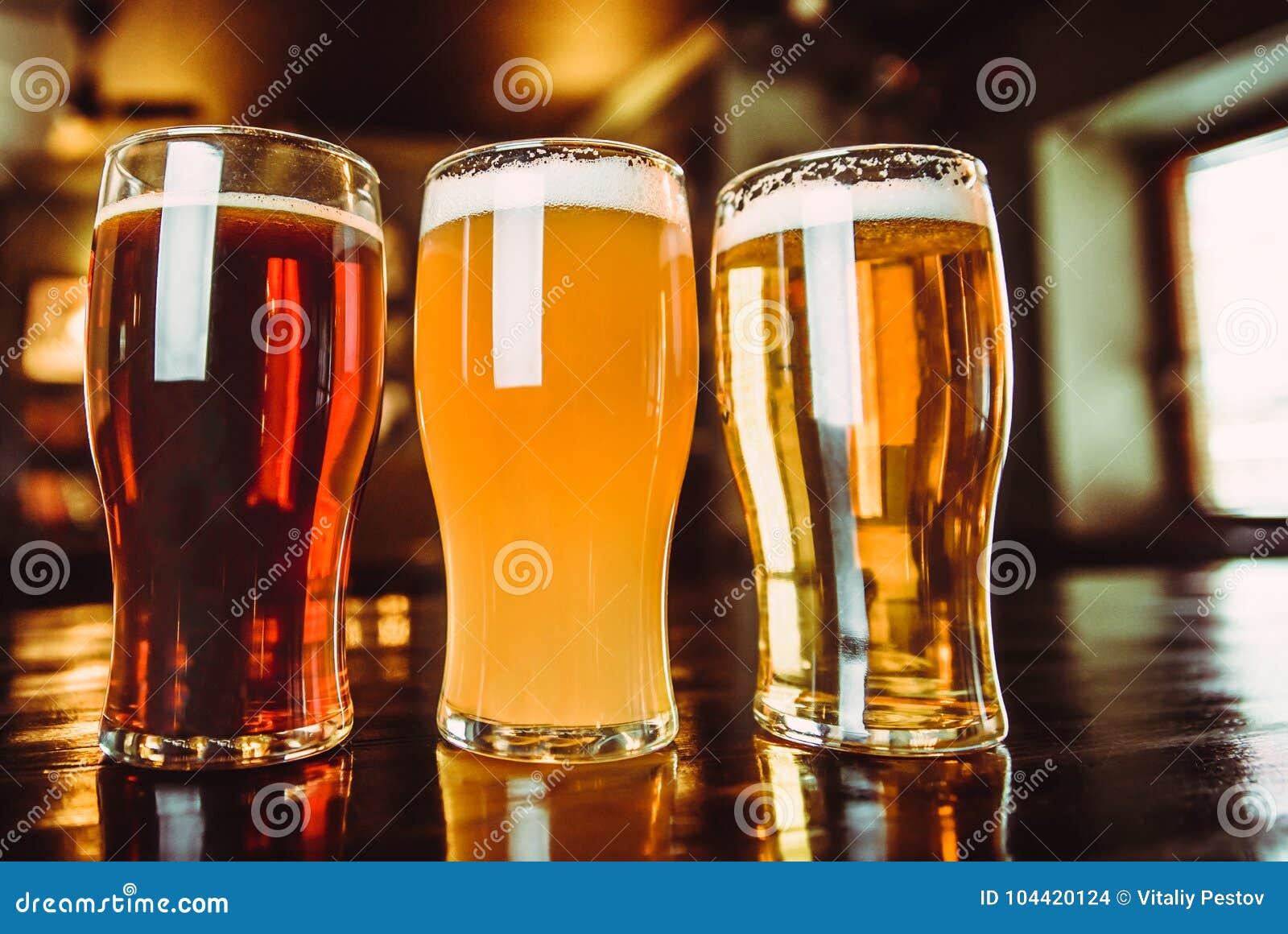 Vetri di birra leggera e scura su un fondo del pub
