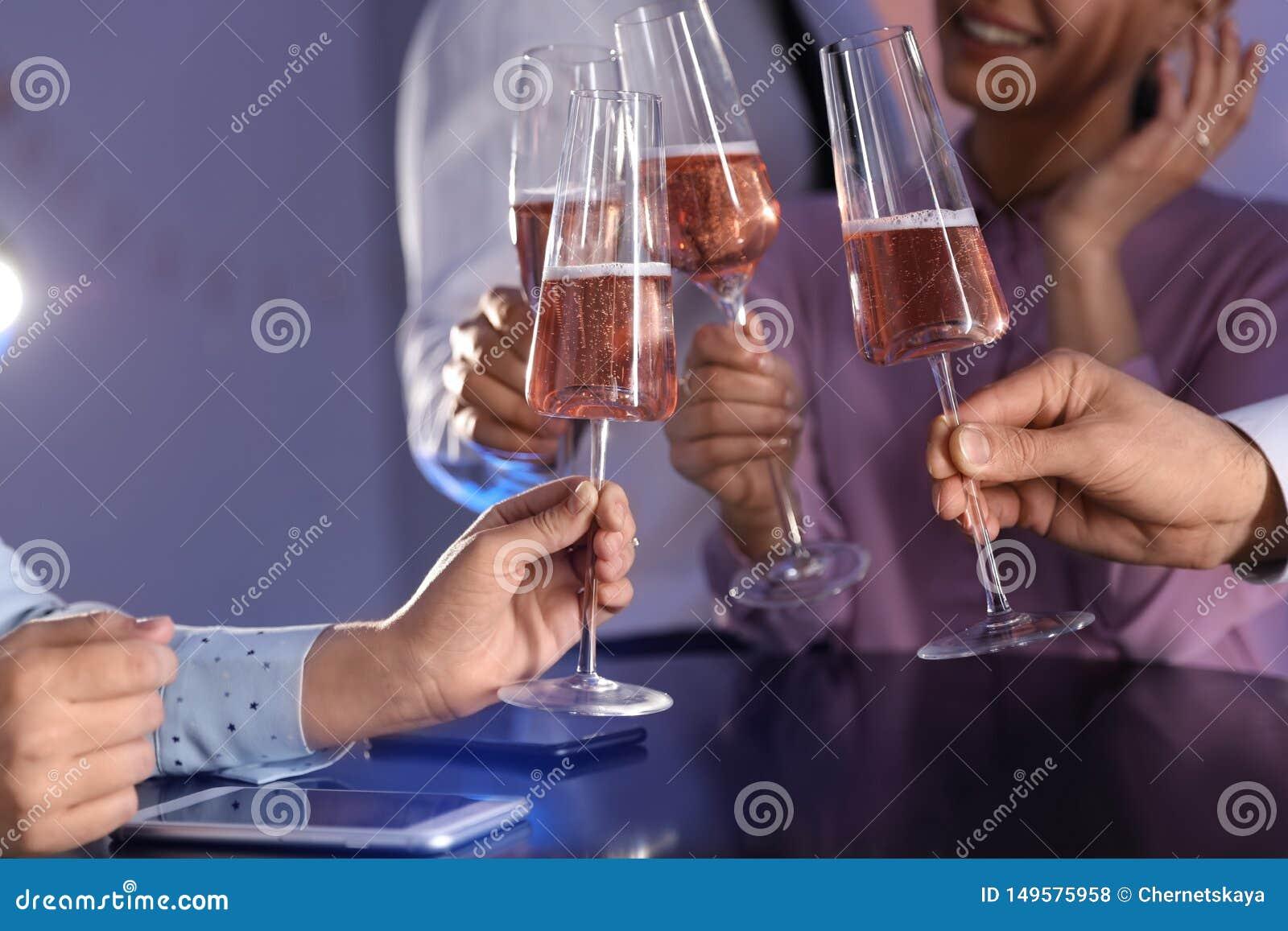 Vetri tintinnanti degli amici di champagne alla tavola in ristorante