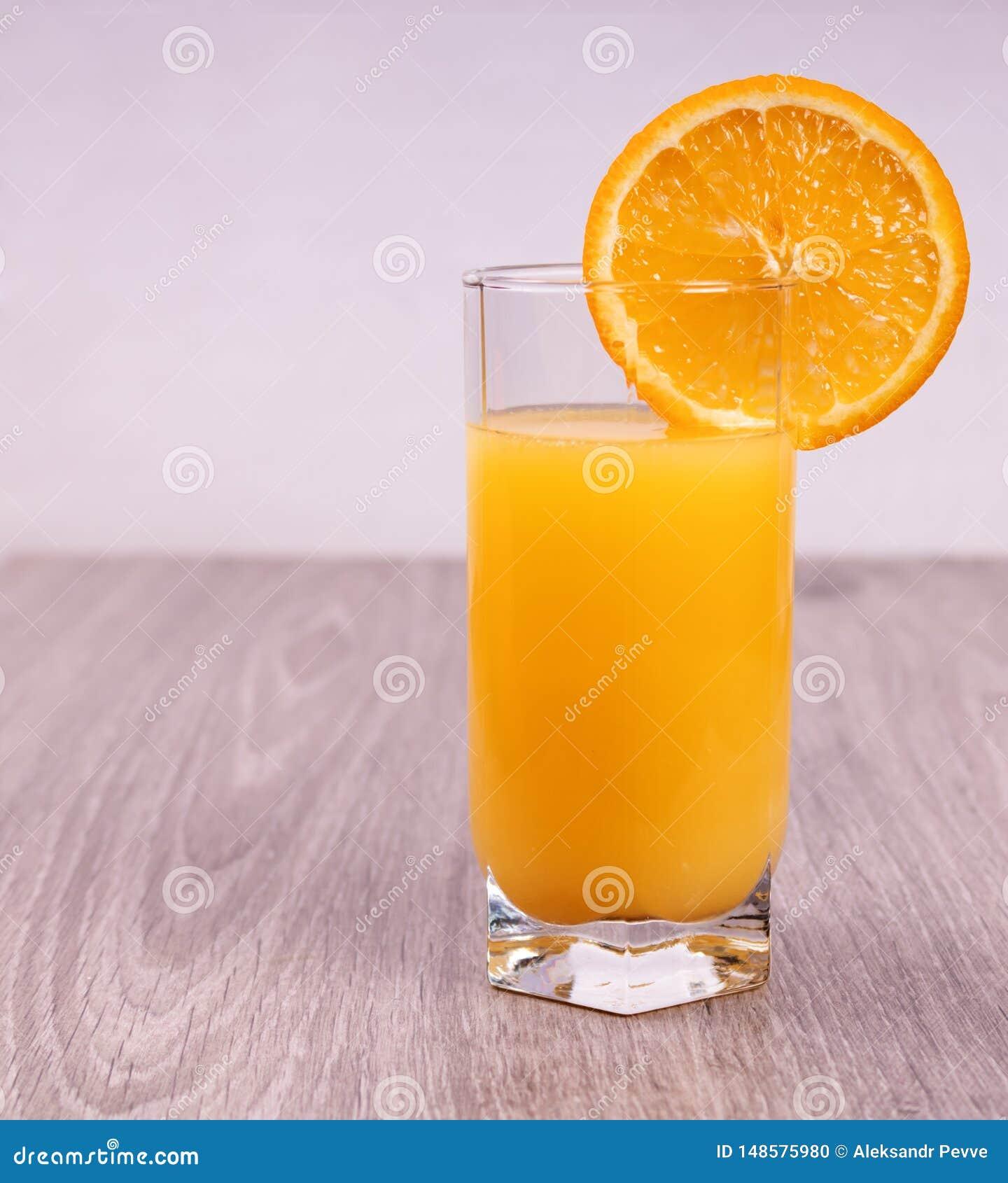 Vetro con la fetta arancio su fondo di legno leggero