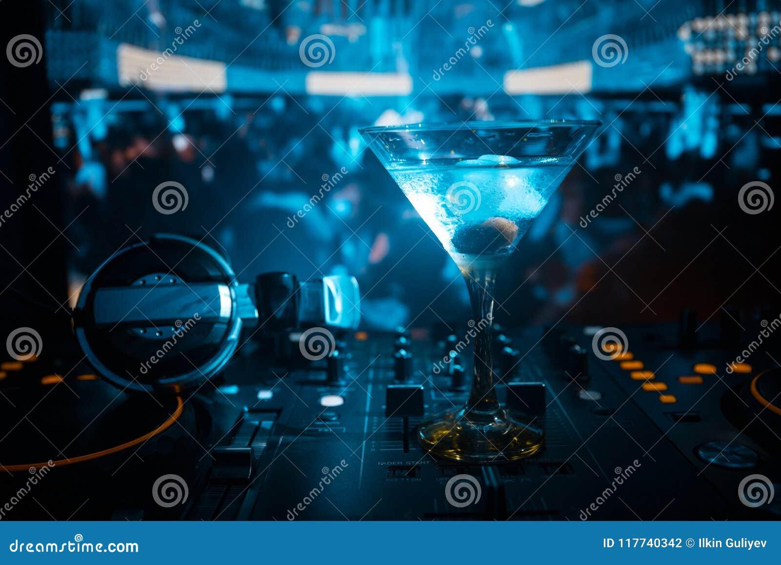 Vetro con martini con oliva dentro sul regolatore del DJ in night-club Console del DJ con la bevanda del club al partito di music