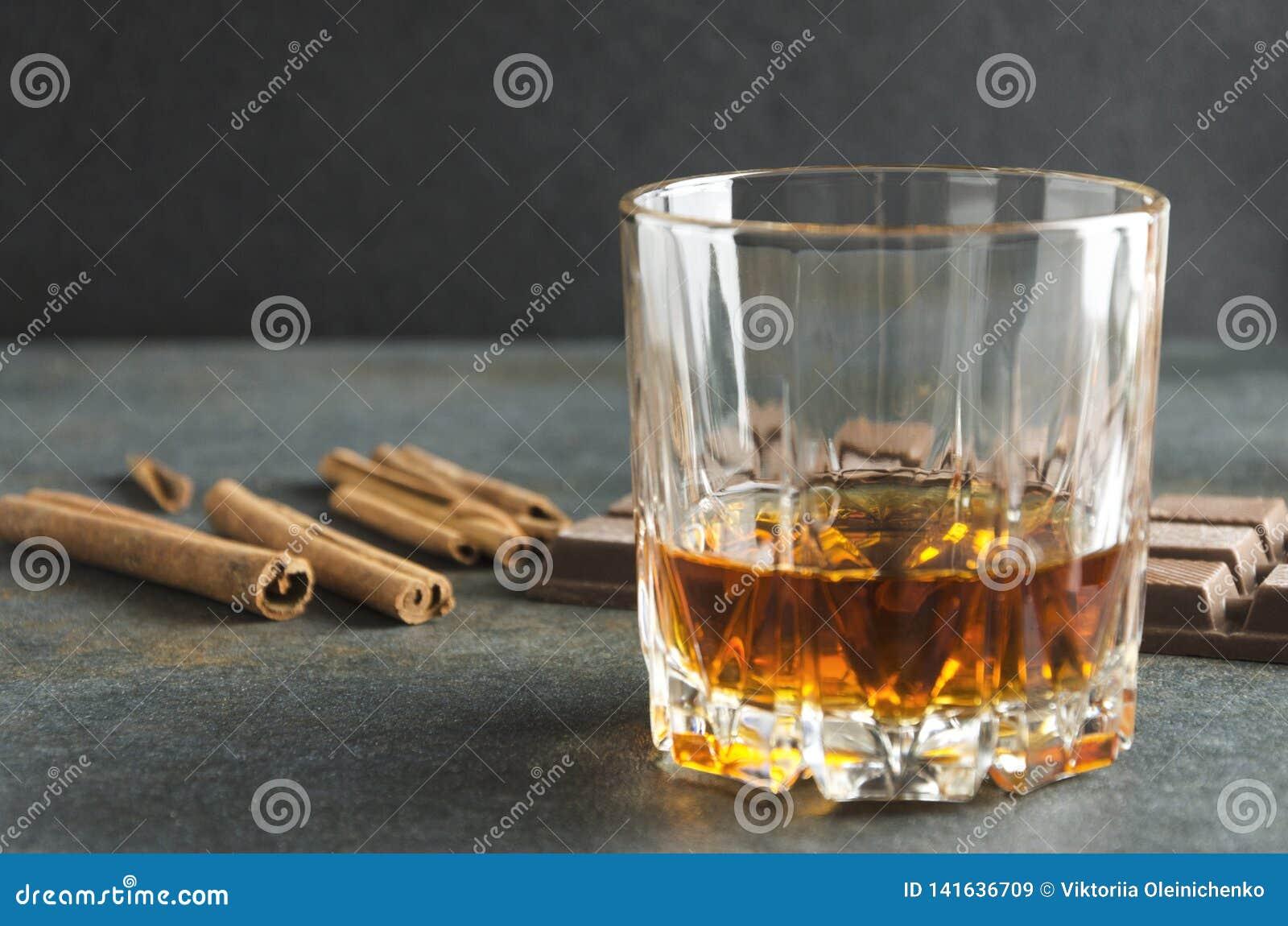 Vetro del reggiseno del brandy, della cannella e del cioccolato sulla tavola grigia Colpo del primo piano