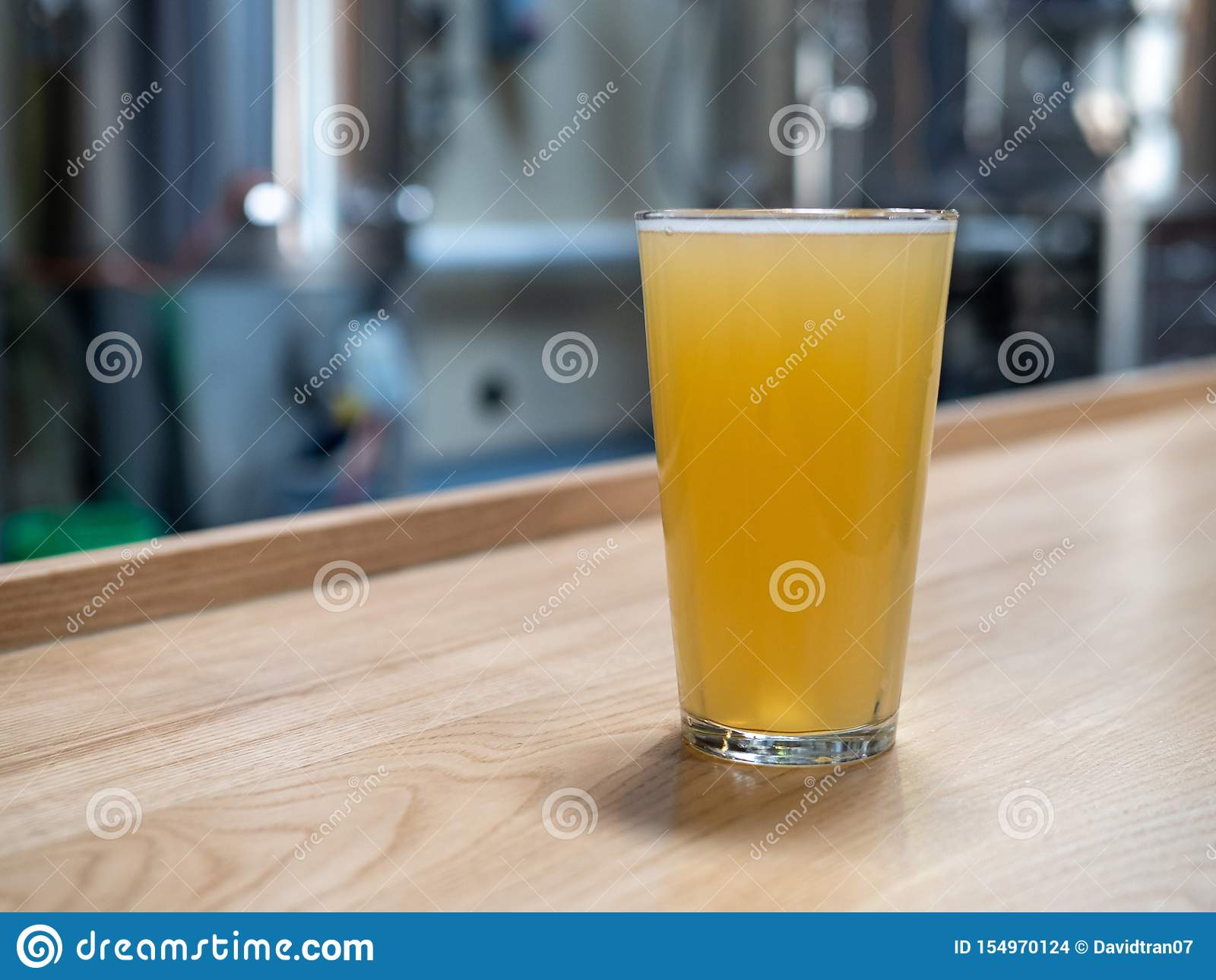 Vetro della pinta di birra bionda davanti ai tini di fermentazione ed alle attrezzature della fabbrica di birra