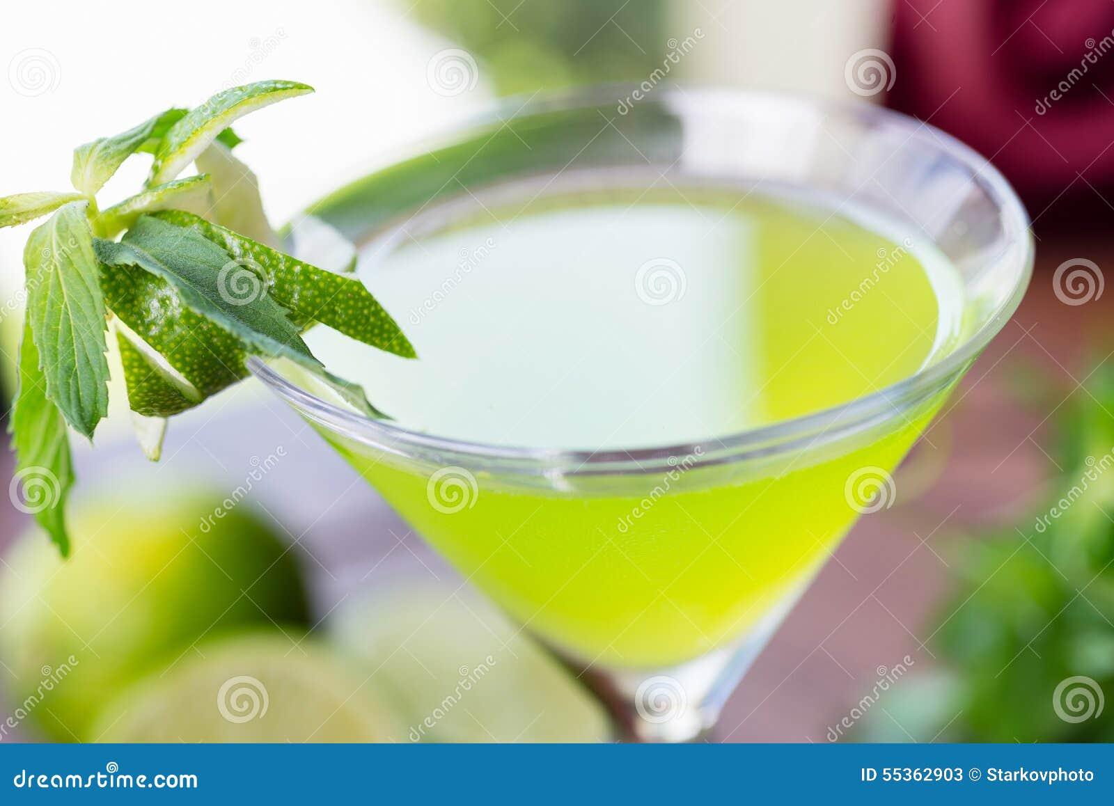 Vetro di rinfresco della limonata fredda della calce con la menta su una tavola di legno in un ristorante con una decorazione cre