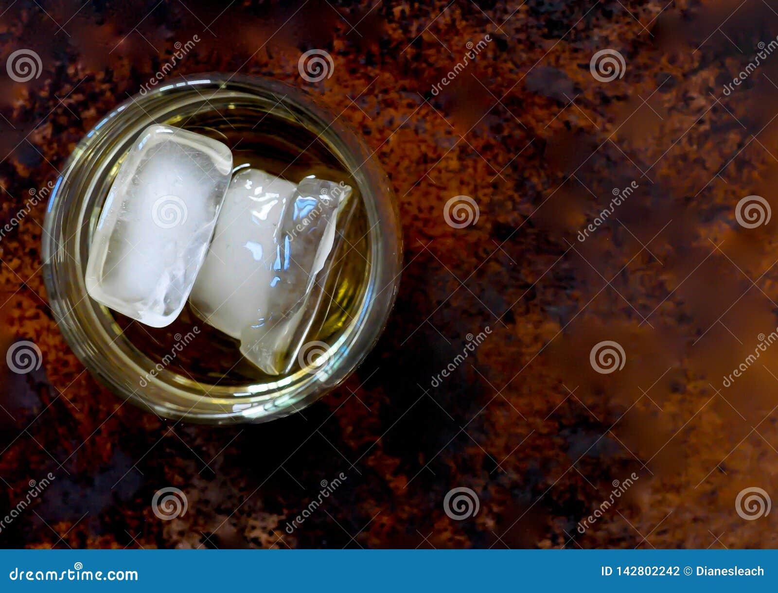 Vetro di scozzese con tre cubetti di ghiaccio, lasciato del centro, su un fondo marrone