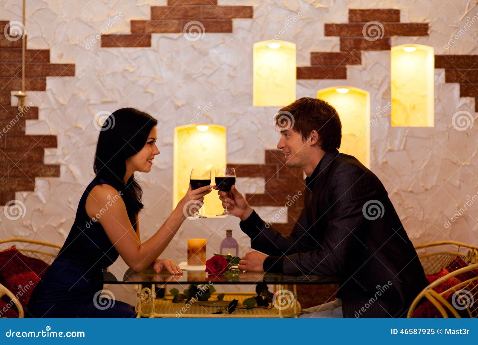 Vetro romantico della bevanda della data delle giovani coppie felici di