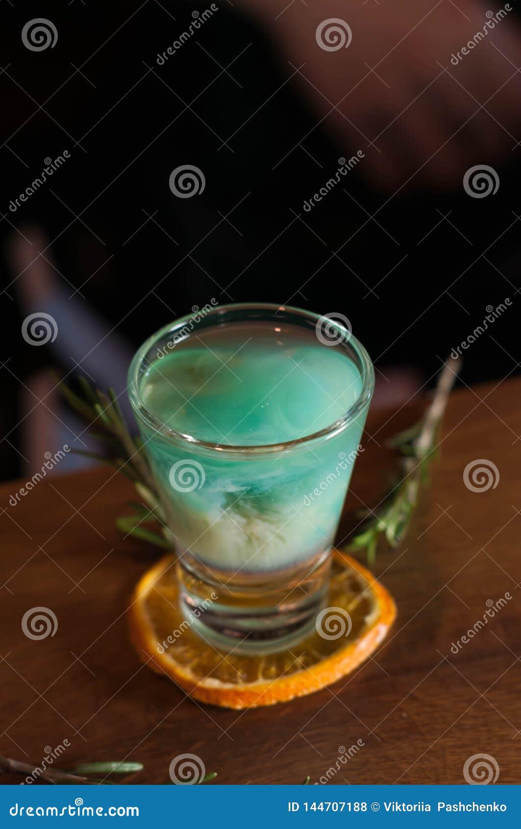 Vetro sparato con la bevanda blu dell alcool sulla fetta arancio secca con i rosmarini