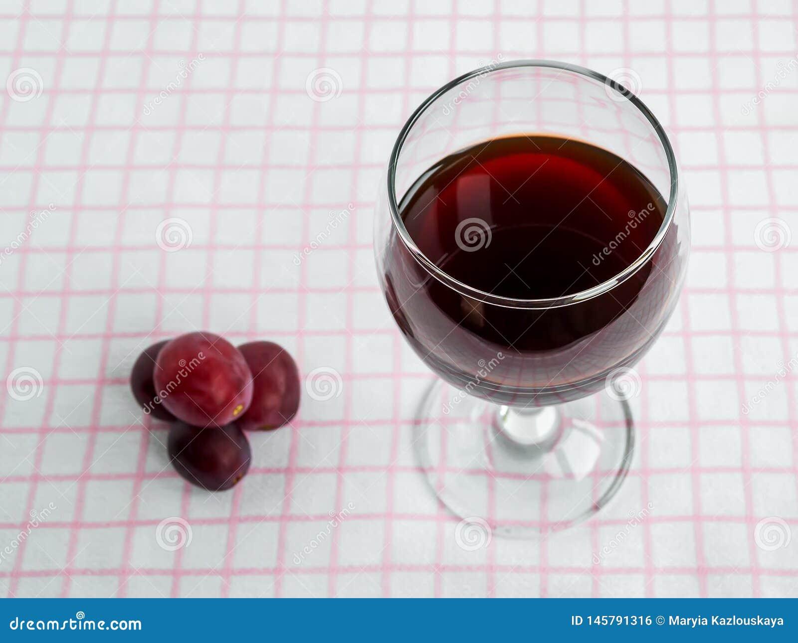 Vetro trasparente con vino rosso e poca uva rossa dolce sulla tovaglia a quadretti rosa bianca Front View