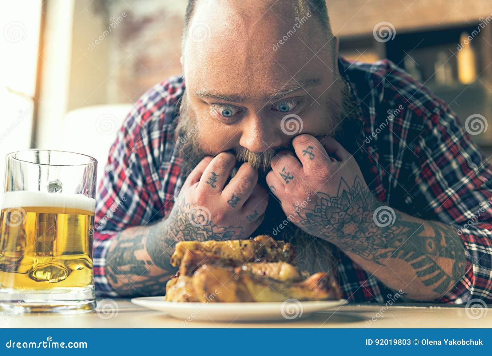 Vette mens die bij vlees met eetlust staren